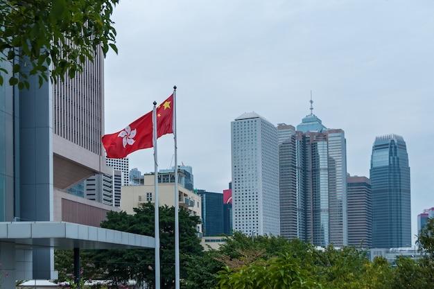Hongkong 29. januar 2016: wolkenkratzer der stadt sind berühmte wahrzeichen von hongkong. flagge von hongkong. hongkong ist eines der am dichtesten besiedelten gebiete der welt.