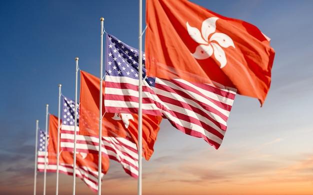 Hongkong- und usa-flaggen, die am bewölkten himmelhintergrund winken
