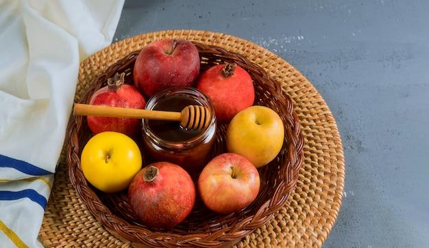 Honig auf apfel und granatapfel mit honigsymbolen des jüdischen neuen jahres rosh hashanah.