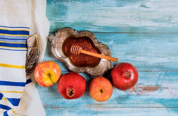 Honig auf dem granatapfel und den äpfeln. jüdisches neujahrsfest yom kippur und rosh hashanah kippah yamolka und shofar