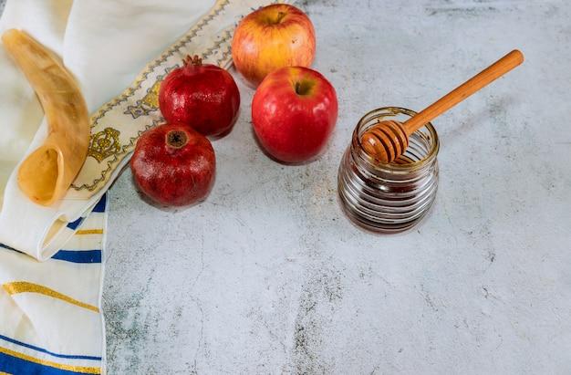 Honig auf dem granatapfel und den äpfeln.