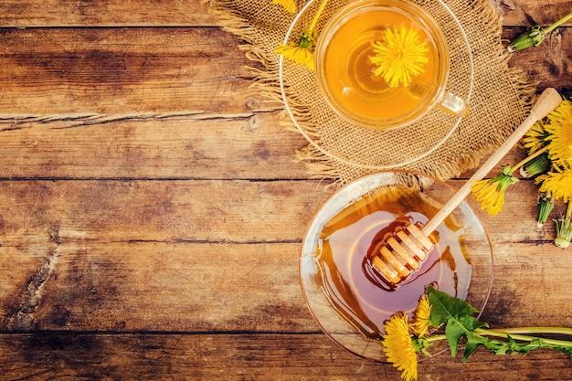 Honig aus löwenzahn und einer tasse tee. selektiver fokus