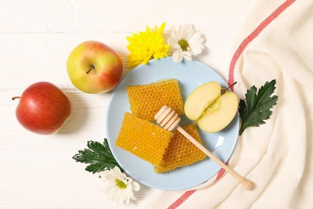 Honig, blumen und äpfel auf weißem hölzernem hintergrund, kopienraum