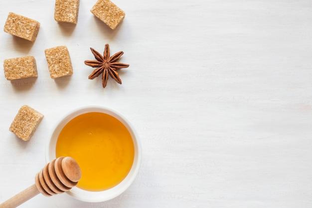 Honig, brauner zucker und sternanis auf hellem hintergrund