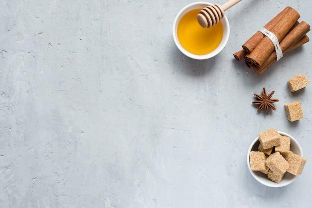 Honig, brauner zucker und sternanis mit zimt auf hellem hintergrund