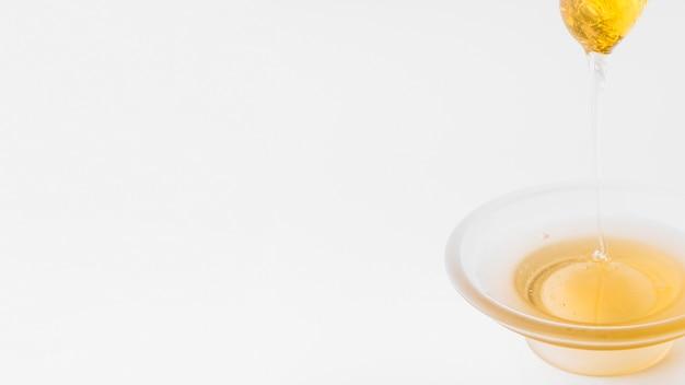 Honig, der in schüssel vom schöpflöffel auf weißem hintergrund tropft