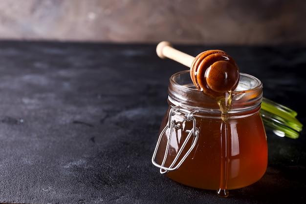 Honig, der voll von einem schöpflöffel in das glas frischen honig auf dunklem steinhintergrund tropft