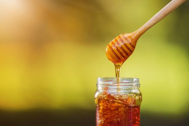 Honig, der vom honigschöpflöffel auf natürlichem hintergrund tropft