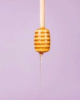 Honig, der von einem hölzernen honigschöpflöffel auf purpurrotem hintergrund tropft