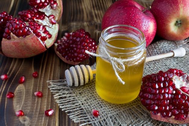 Honig, granat und äpfel auf dem rustikalen hintergrund