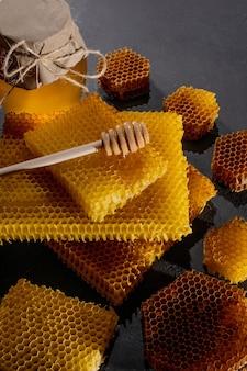 Honig-hintergrund. natürliche honigwabe und ein holzlöffel. auf schwarzem rustikalem tisch.