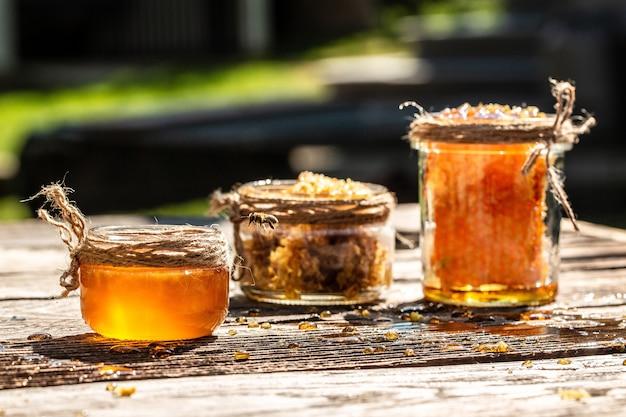 Honig im glas mit biene, die auf holztisch auf hintergrundwaben mit vollen zellen des honigs fliegt