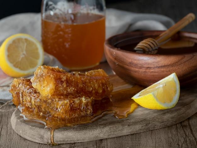 Honig im glas mit bienenwabe und hölzerner drizzler mit zitrone auf holztisch. dunkler hintergrund