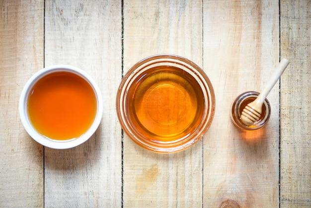 Honig im glas mit hölzernem schöpflöffel auf holz
