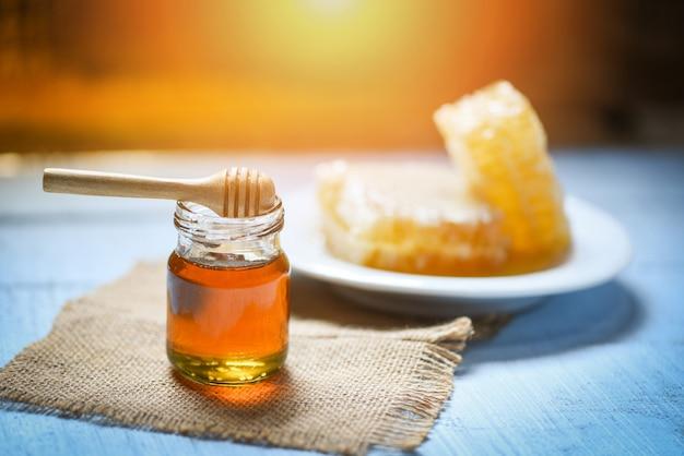 Honig im glas mit hölzernem schöpflöffel und bienenwabe auf natürlichem gesundem lebensmittel der platte auf tabelle