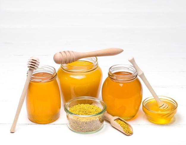 Honig im glas mit honigschöpflöffel auf hölzernem hintergrund