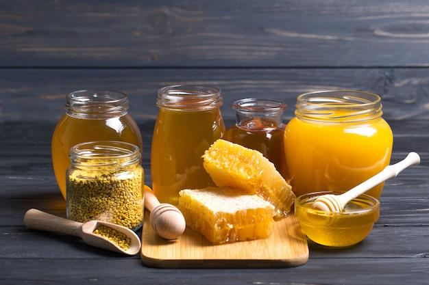 Honig im glas mit honigschöpflöffel auf holztisch