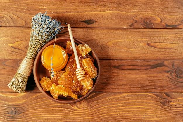 Honig im glas mit honigschöpflöffel auf weinleseholz