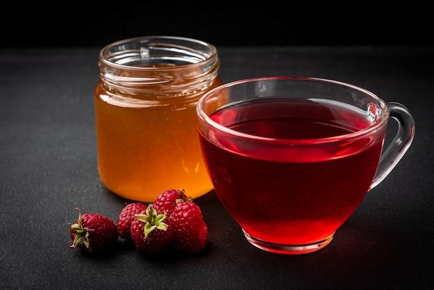 Honig im glas und frische himbeere auf schwarzem hintergrund.