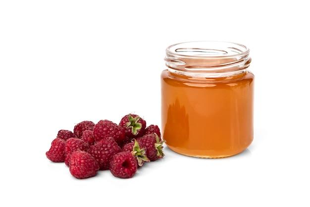 Honig im glasglas und in der frischen himbeere lokalisiert auf weißem hintergrund.