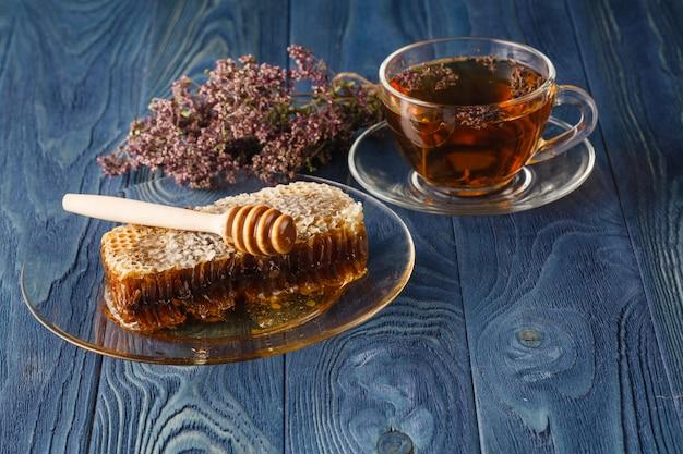 Honig im kamm und blumen auf dem tisch