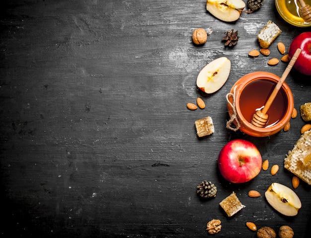 Honig im topf mit scheiben reifer äpfel und nüsse.
