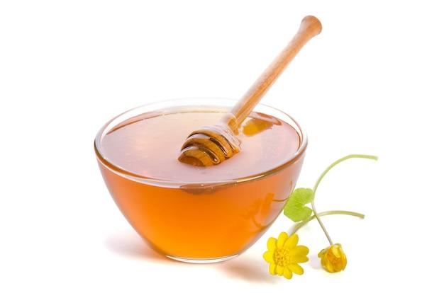 Honig in der glasschale mit schöpflöffel isoliert