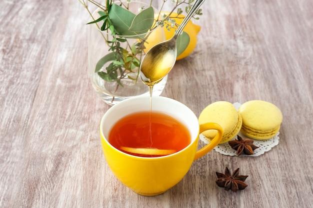 Honig in die tasse auf holz gießen