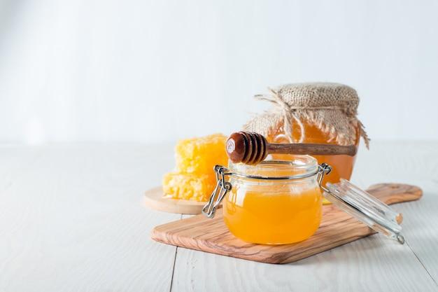 Honig in einem glas auf hölzernem rustikalem hintergrund