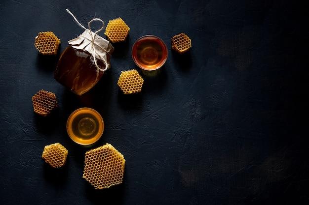 Honig in einem glas und einer wabe. auf einem schwarzen hölzernen hintergrund. freier platz für text. draufsicht.