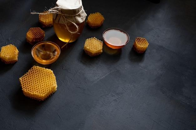 Honig in einem glas und einer wabe. auf schwarzem holzhintergrund. freier platz für text. ansicht von oben.