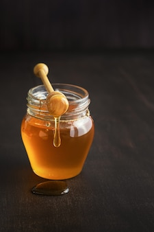 Honig in einem glasgefäß mit honigschöpflöffel auf rustikalem holztischhintergrund. platz kopieren.