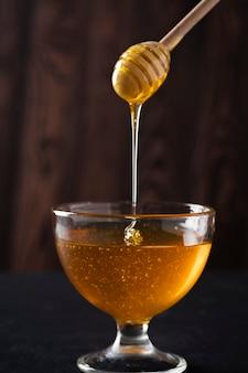 Honig in einem glasschüsselhonigschöpflöffel auf einem dunklen hintergrund. nahansicht