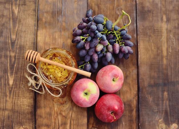 Honig in einem schönen glas, in einer hölzernen löffelspindel, in trauben und in äpfeln auf einem hölzernen hintergrund