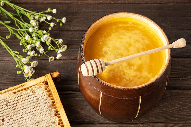 Honig in einer holzwabe und einem honiglöffel