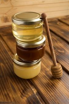 Honig in gläsern auf dem hölzernen hintergrund