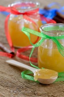 Honig in gläsern auf einem holztisch neben den zimtstangen und einem löffel