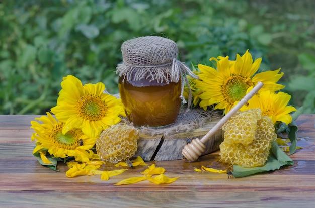 Honig in gläsern und westliche honigbiene. honigbiene auf natur. honig mit fliegender honigbiene