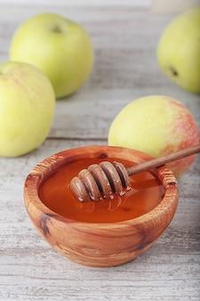 Honig in holzschale mit honiglöffel und grünen äpfeln auf weißem vintage-holzhintergrund