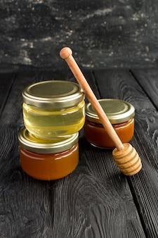 Honig in kleinen gläsern auf schwarz. lage vertikal. nahansicht.