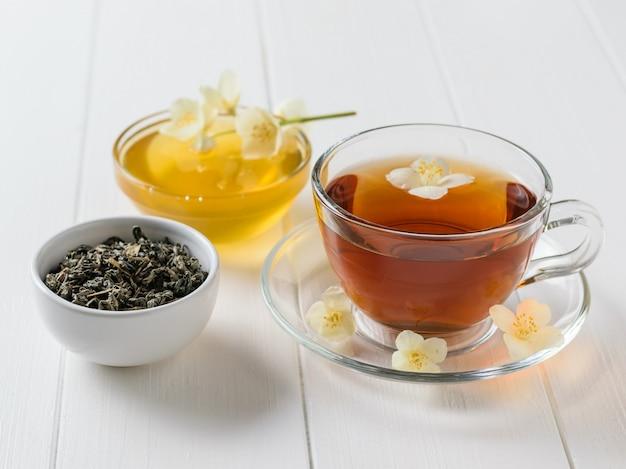 Honig, kräutertee und jasmin auf einem weißen holztisch
