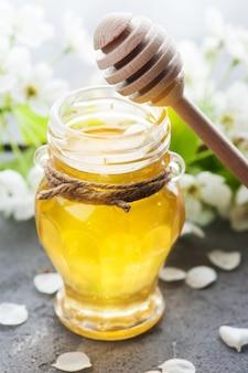 Honig mit blüten und holzlöffeln