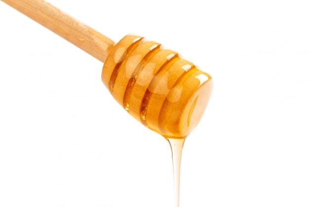 Honig mit dem hölzernen drizzler getrennt auf weiß