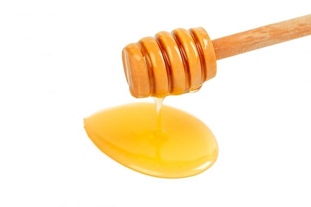 Honig mit dem hölzernen drizzler lokalisiert auf weißem hintergrund