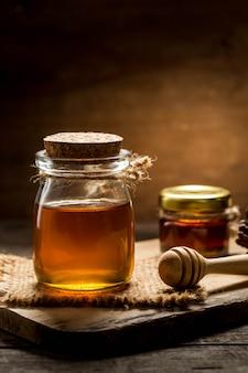 Honig mit schöpflöffel auf hölzernem hintergrund