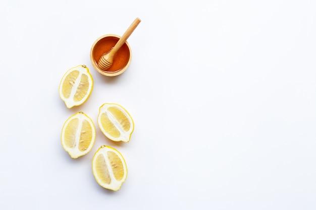 Honig mit zitrone auf weißem hintergrund. platz kopieren