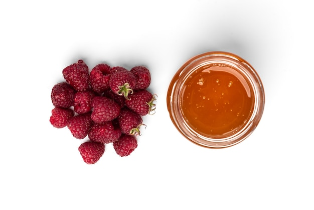 Honig oder marmelade im glas und in der frischen himbeere lokalisiert auf weißem hintergrund.