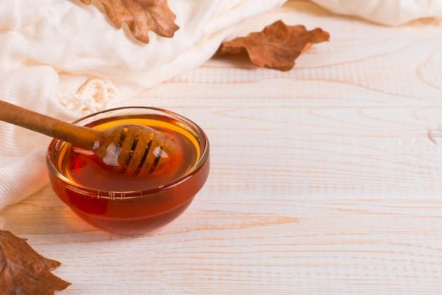 Honig, peitsche, glas, schal, trockene blätter. rustikales süßes herbstfoto, weißer hölzerner hintergrund, copyspace.