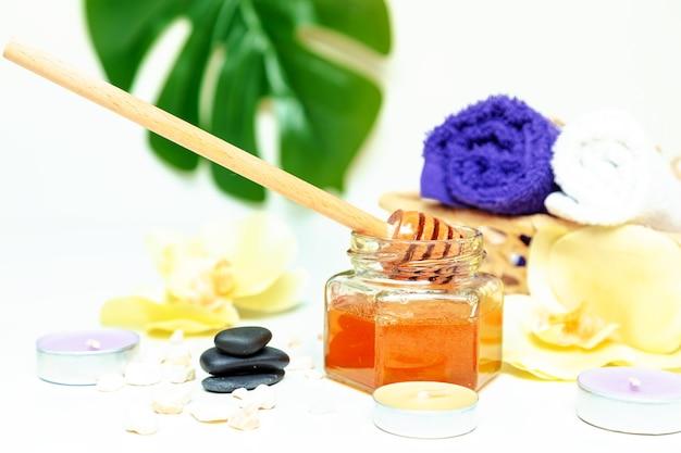 Honig-spa-behandlung. goldhonig im glas, orchideenblüten, handtücher und duftkerzen. natürliche häusliche hautpflege.