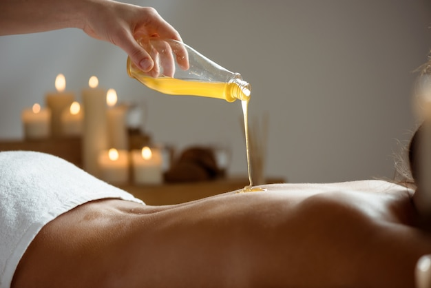 Honig strömt auf den nackten rücken der frau im spa-salon.